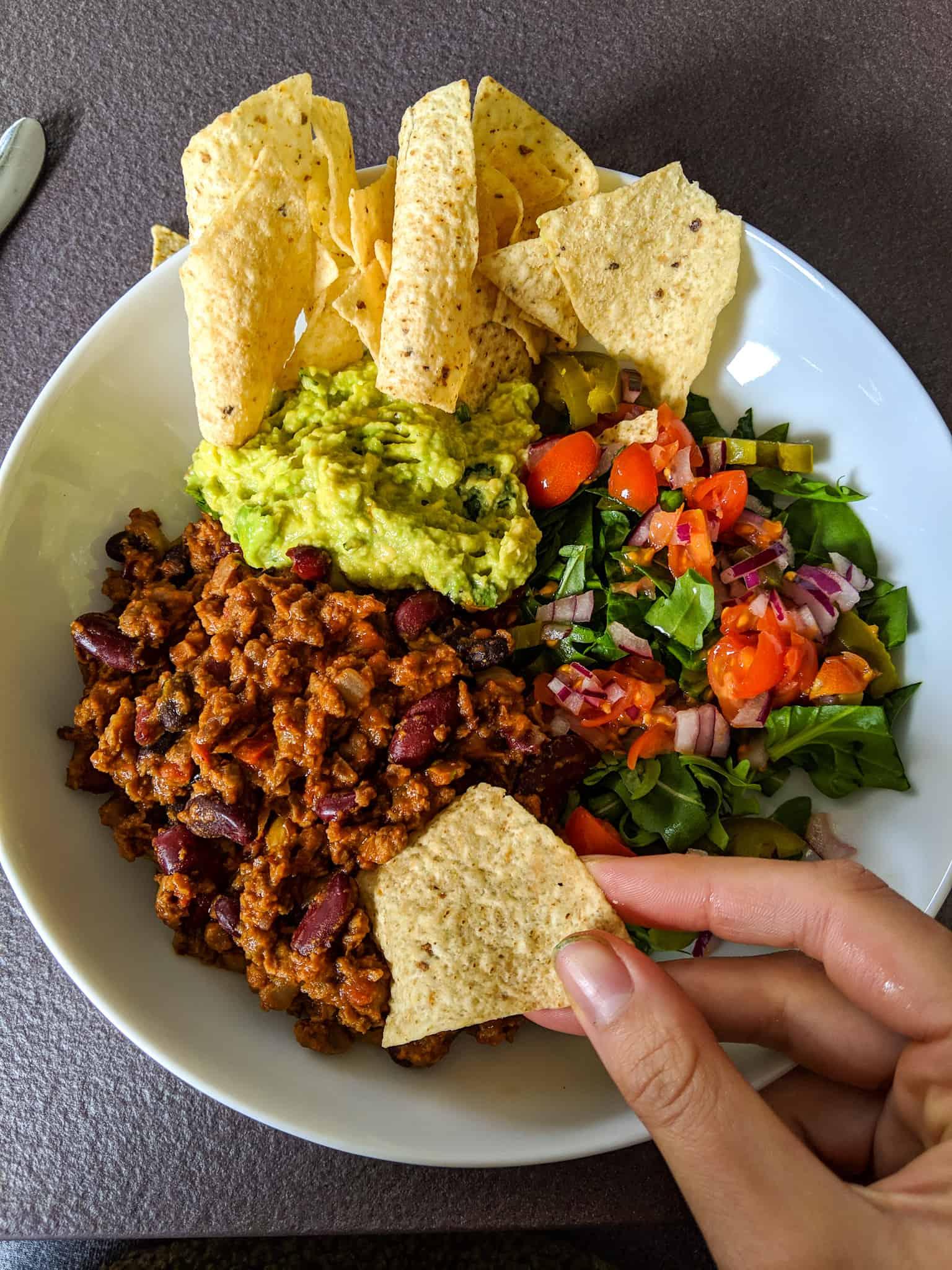 Vegan chilli con carne with pico de gallo, guacamole, and tortilla chips