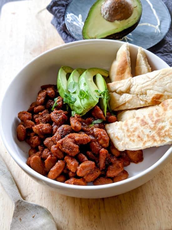 Mexican pinto beans with tortillas and avocado.